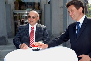 Sourire aux lèvres, Philippe Egger et Henri de Castries dévoilent au moyen d'un bouton rouge la nouvelle plaque de l'entreprise apposée sur le bâtiment principal d'AXA.