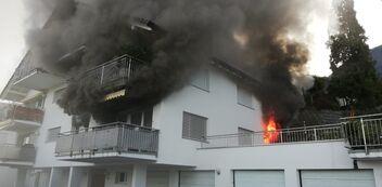 Brennender Wohnblock, schwarzer Rauch quillt aus einem Balkon.